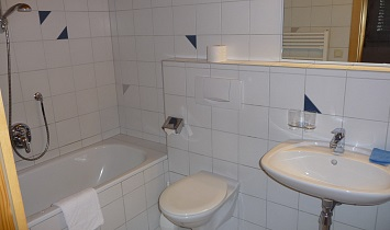 Bathroom with bath, WC and wash basin in the Classic apartment with gallery